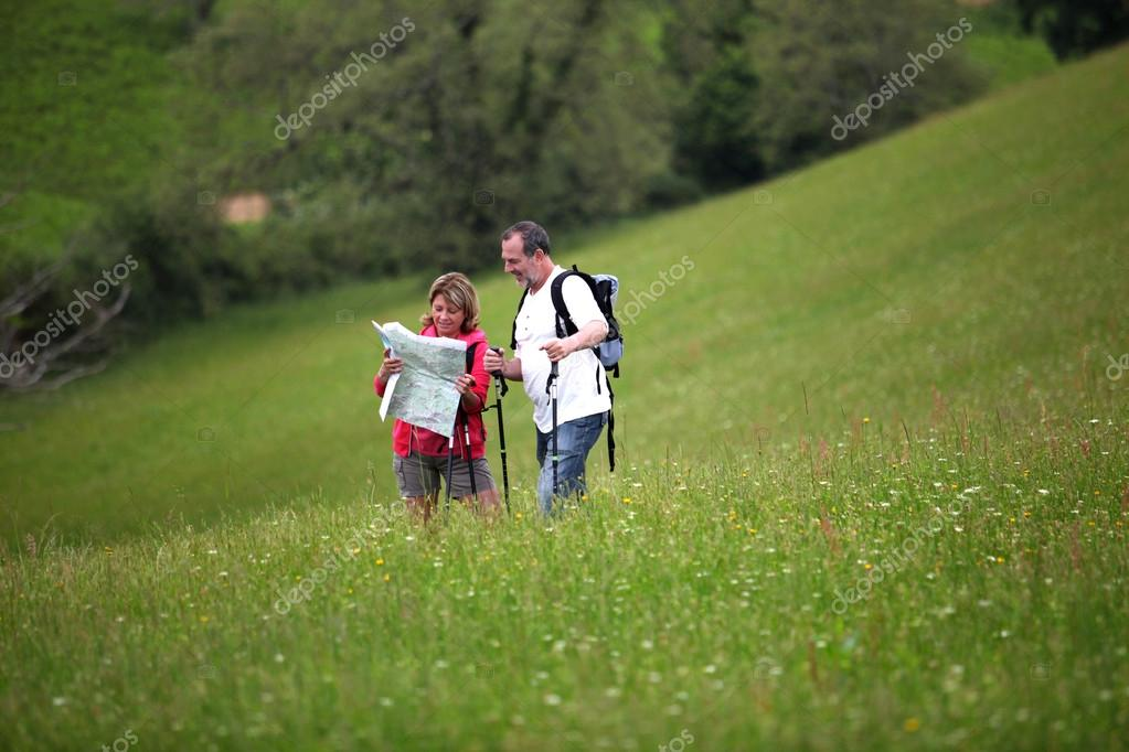 Senior hikers reading map in country field