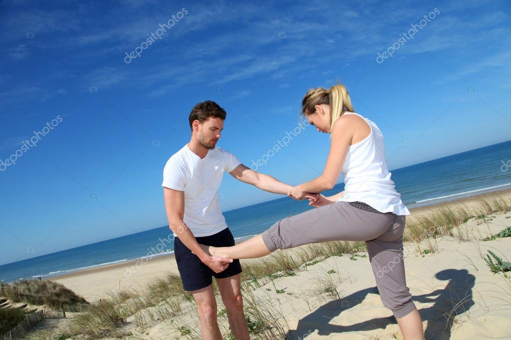 Man helping girl stretching out