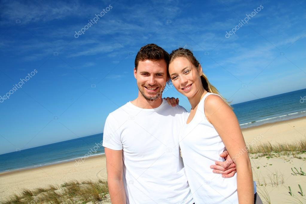 Smiling couple in fitness outfit standing on the beach