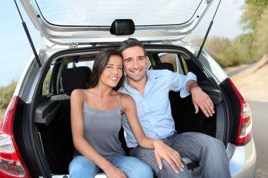 Happy couple sitting in car open trunk