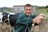 Fotografia pastore in piedi davanti al bestiame nella fattoria
