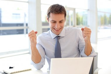 Businessman with successful expression in front of laptop