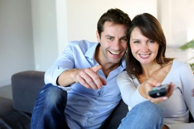 Couple sitting in couch choosing tv program