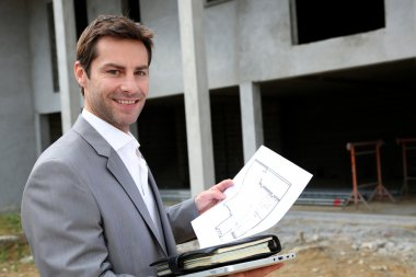 Construction salesman checking building site
