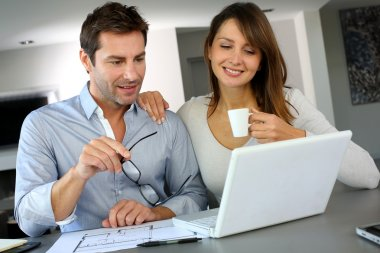 Couple at home looking at future home blueprint