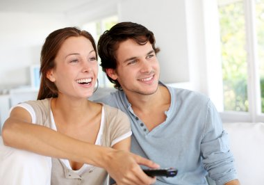 Couple sitting in sofa with remote control in hands