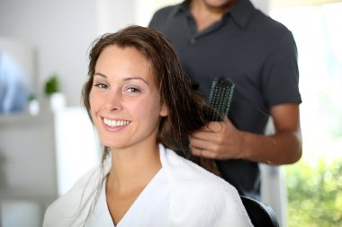 Woman having her hair dried by hairdresser