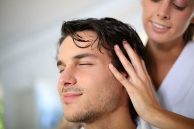 Hairdresser doing head massage to customer