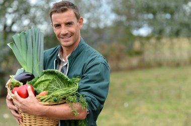 Portrait of smiling farmer holding vegetables basket