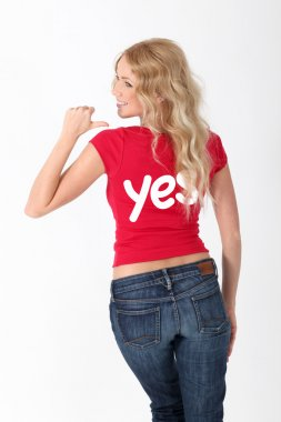 Woman wearing red shirt with YES word on it