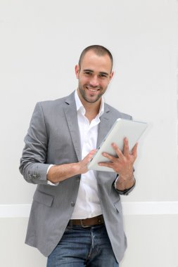 Cool businessman using electronic tablet