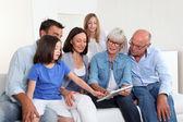 Fényképek 3 generációs családi ül a kanapén, elektronikus tabletta