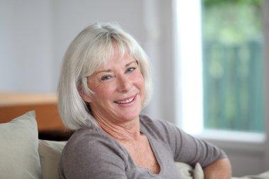 Portrait of smiling senior woman sitting in sofa