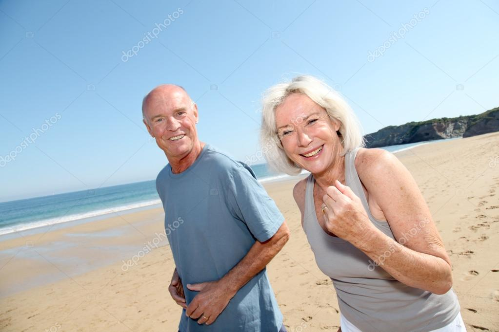 Senior couple jogging on a sandy beach