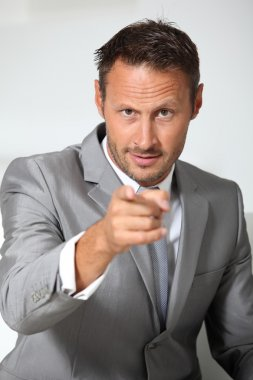 Businessman pointing finger at camera