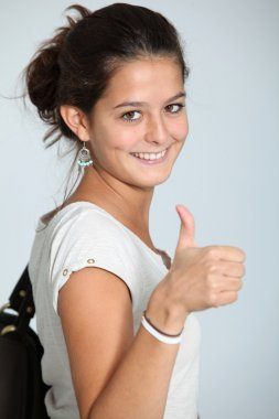 Closeup of teenaged girl wth thumb up