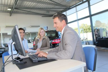 Car seller and couple of buyers signing contract