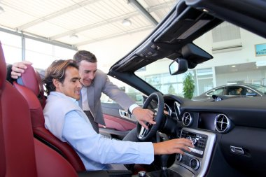 Car seller showing interior details to purchaser