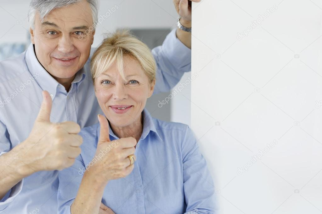 Senior couple showing thumbs up