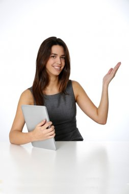 Young woman with tablet pointing at message board