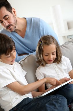 Children with daddy at home using digital tablet