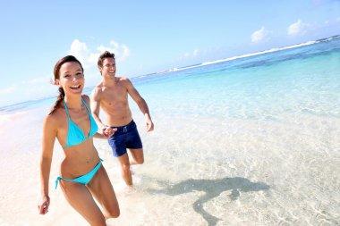 Couple running on a sandy beach stock vector