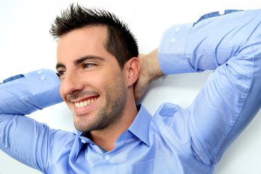 Cheerful man with stretched arms behind head