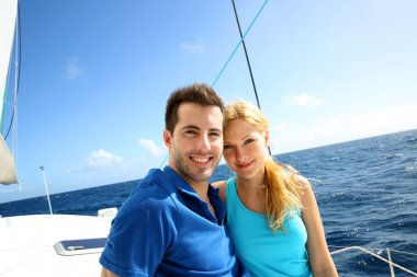 Portrait of couple sitting on the top of sailing boat