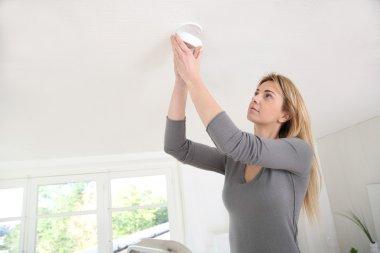 Woman setting up fire alarm inside house
