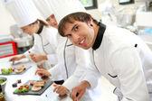 Fotografie usmívající se mladý muž v kuchyni restaurace