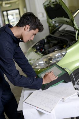Students doing car diagnostic with computer