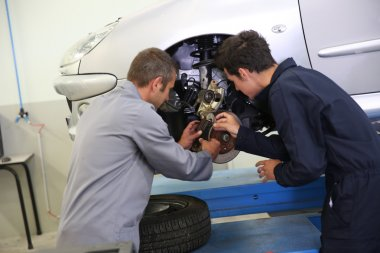 Instructor showing student how to change car brakes