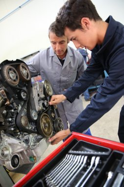 Teacher and student in auto mechanics training class