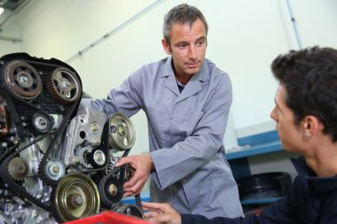 Trainer teaching student how to fix car engine