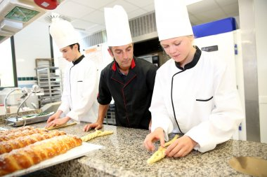 Baker with students in kitchen
