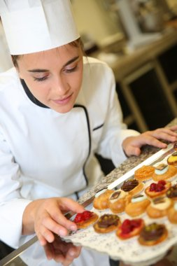 Pastry cook holding tray of pastries