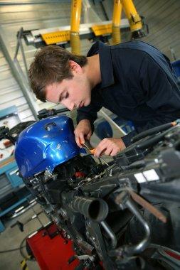 Teenager repairing motorbike