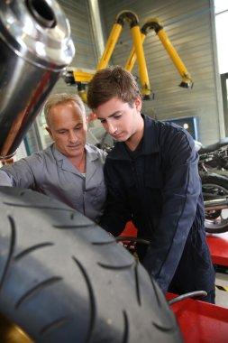 Teacher with students in mechanics
