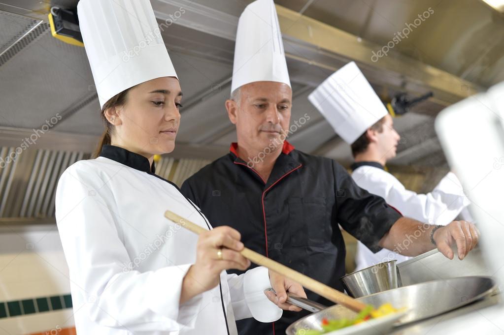 Chef teaching student how to prepare wok dish