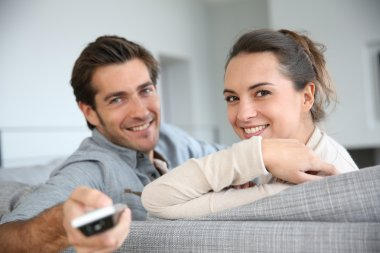 Couple sitting in sofa and watching movie