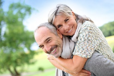 Senior man giving piggyback ride to woman