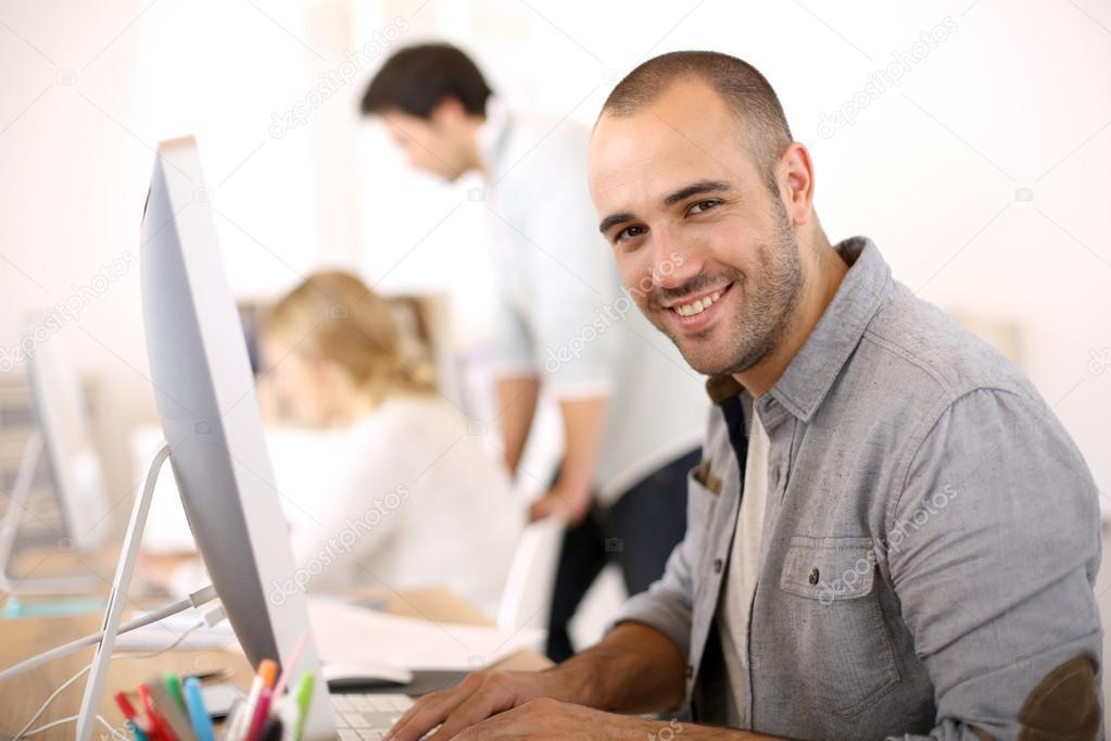 Guy sitting in front of desktop computer