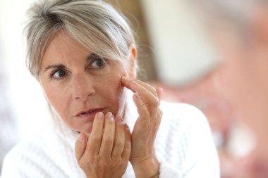 Woman applying anti-wrinkles cream