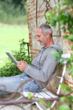Mature man using tablet on a bench