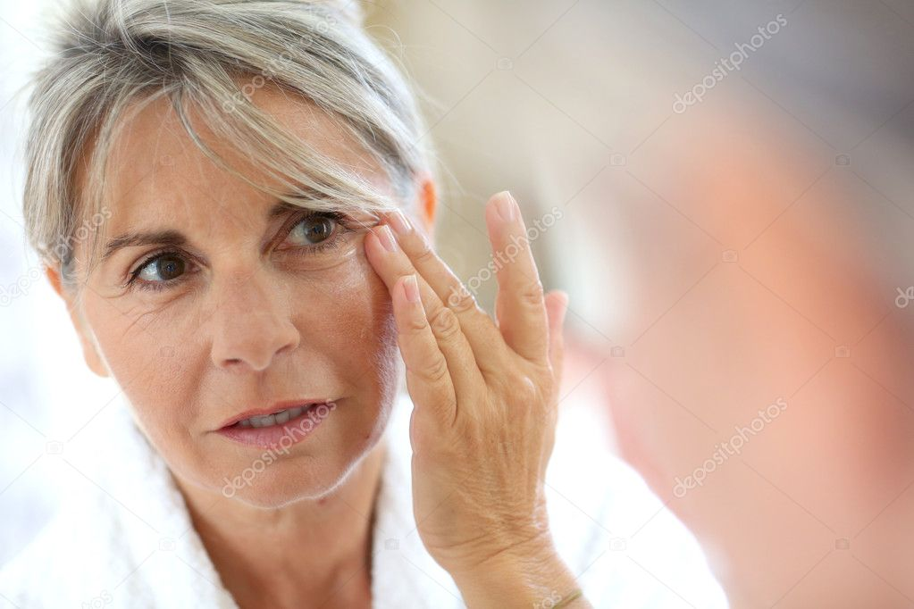 Woman applying anti-wrinkles cream