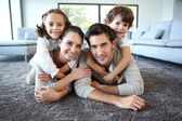 Smiling family on carpet