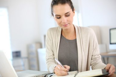 Businesswoman writing on agenda