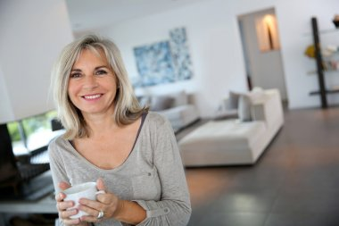 mature woman at home drinking tea