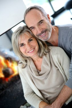 Senior couple enjoying fireplace