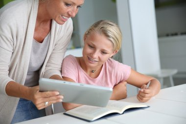 Mother helping girl with homework